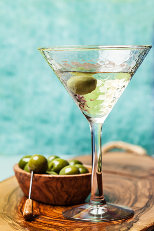 Martini cocktail with green olive on wooden board Stock Photo