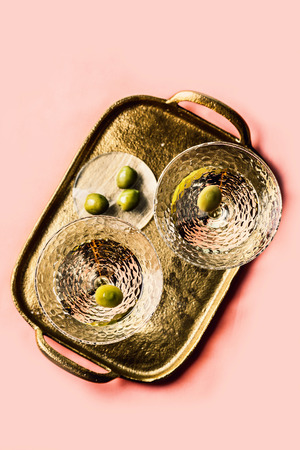 Martini cocktail with green olive on gold-colored tray Stock Photo