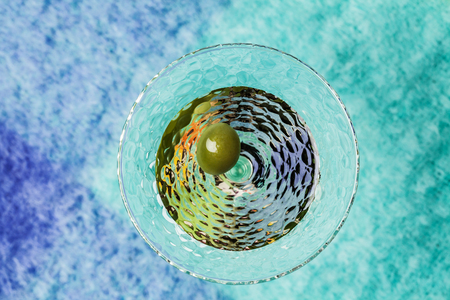 Martini cocktail with green olive on bright blue background Stock Photo