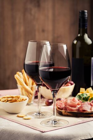 Red wine with charcuterie, cheese, grapes and snacks 写真素材