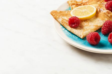 Folded pancakes with lemon slices and raspberries on white marble background Stock Photo