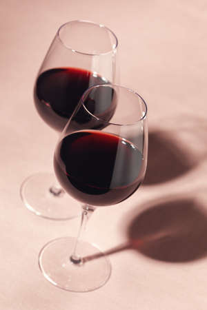 Two glasses of red wine on pink background
