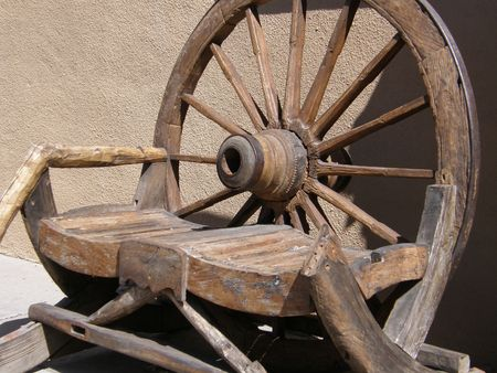 sitting on the ground: Wooden Wagon Wheel Stock Photo