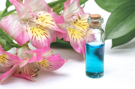 Blue essential oil tincture on white wooden table background. Front view. Herbal medicine. Alternative medicine.