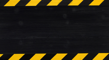 Under construction concept Warning tape frame on black wooden surface background with copy space.