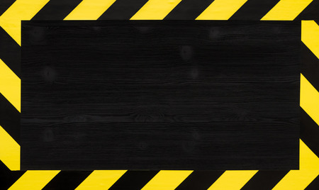 Under construction concept background. Warning tape frame on black wooden surface background with copy space.