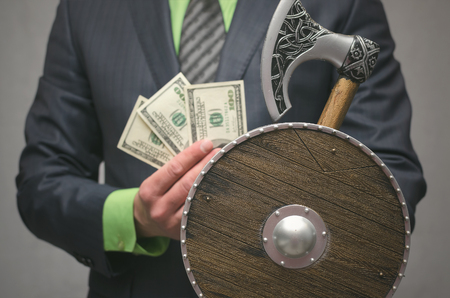 Businessman holds in hand a toy viking axe weapon and shield. Life or finance insurance agent. Money deposite safety agent.