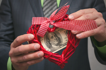 Red heart shape and one hundred dollars in businessman hands. Love for money. Greedy man. Miser.