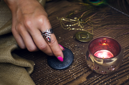 Zodiac talisman in female hand in the lights of burning candle. Horoscope wheel. Astrology.