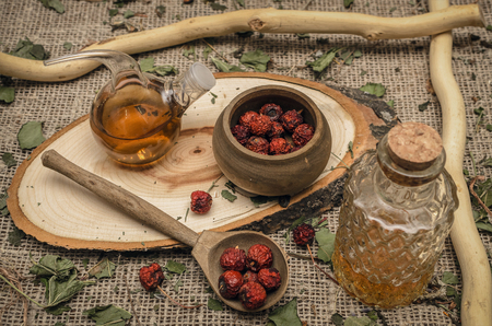 Herbal medicine concept. Dry wild apple tree berry in the jar and apple juice in the bottle on brown wooden table background.