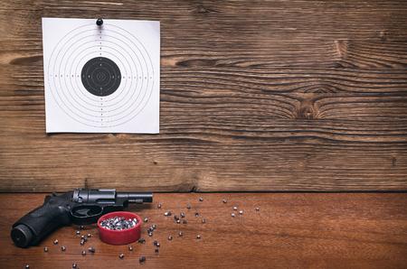 Pistola pistola e bersaglio di carta. Pratica di tiro. Fondo del poligono di tiro con lo spazio della copia. Archivio Fotografico