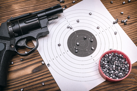 Gun pistol and paper target with scattered bullets around. Shooting practice. Shooting range background with copy space.