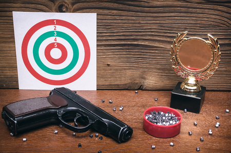 Best shooter award background with copy space. Winner in shooting. Gun, paper target and gold medal. Shooting range.