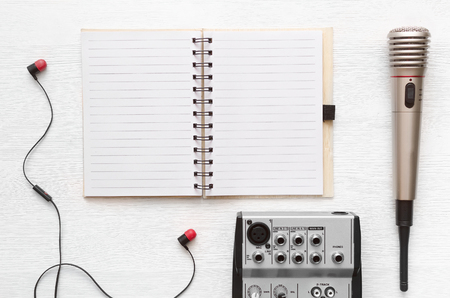 Audio recording studio desk table. Karaoke mock up. Song lyrics. Microphone, audio sound mixer, blank page notepad and headphones on white table background with copy space.