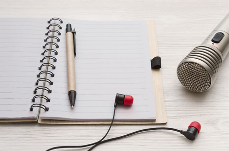 Audio recording studio desk table. Karaoke mock up. Microphone, headphones and blank page notepad with copy space for song lyrics on white table background. Stock Photo