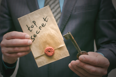 Opening of Top secret concept. Disclosure of secrets. Top secret documents or message and a decryption key in businessman hands. The access key to unraveling.