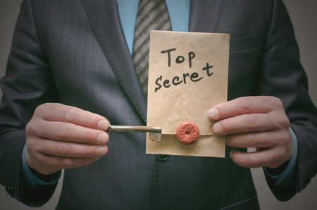 Top secret concept. Top secret documents or message and a decryption key in businessman hands. The access key to unraveling. Discrimination of secret information.