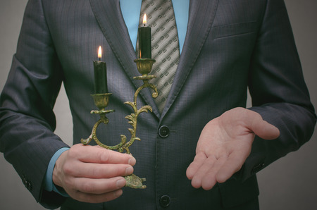Business man holds a burning candle in a candlestick and illuminates the path to success. Leadership concept. Business conspiracy. Shadow business. In search of investment.