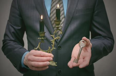 Key to success concept. Businessman holding in hands an old rusty key and a burning candle in candlestick. Explanation of information decryption key. Access to forbidden materials.