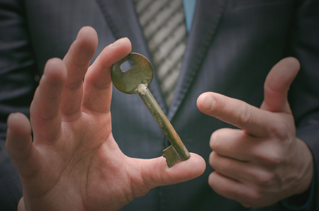 Key to success concept. Businessman holding in hands an old rusty key. Explanation of information decryption key. Access to forbidden materials.