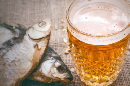Glass of light beer and stockfish on burlap cloth background. Stock Photo