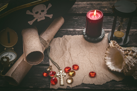 Pirate captain table with crumpled paper page with copy space for treasure map, golden compass, sand watch, scrolls,gemstones and seashell.