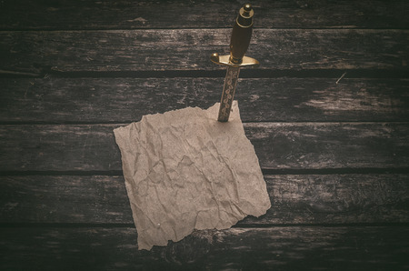 Crumpled brown paper page parchment and the dagger blade thrust in a table. Adventurer treasure hunter or pirate concept background. 版權商用圖片