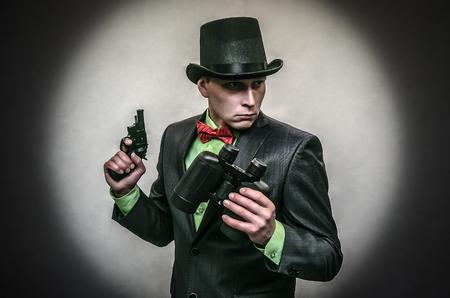 Spy agent. Secret service. Detecive agent holds pistol gun in his hands and binoculars isolated. Retro gangster. Stock Photo