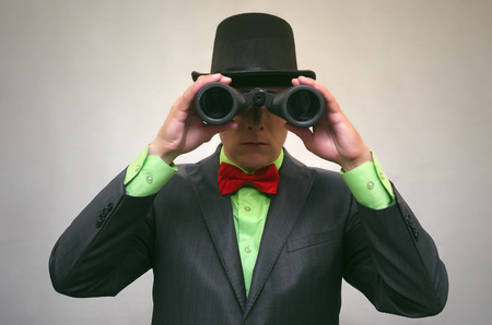 Spy. Secret detecive agent holds binoculars in his hands and looks through him isolated. Retro gangster. Stock Photo