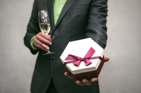 Man in suit holds in one hand a present box and champagne in wineglass in another hand isolated on white. Award ceremony. Stock fotó