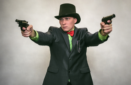 The spy. Secret service. Angry Detecive agent holds pistol gun in his hands aiming and attack. Retro wicked gangster isolated on white background. Stock Photo