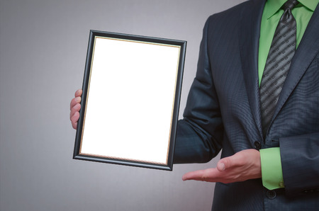 Blank diploma or certificate mock up in businessman hand. Empty photo frame border with copy space. Standard-Bild