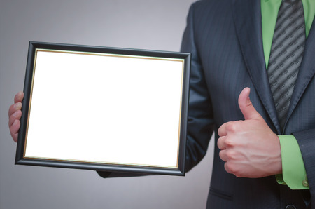Blank diploma or certificate mock up in businessman hand. Empty photo frame border with copy space. Stockfoto