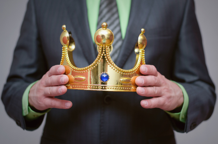 Businessman king holding in hands a gold crown. Award ceremony concept. Winner.