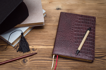Graduate cap, stack of books and school diary book on the wooden school desk.