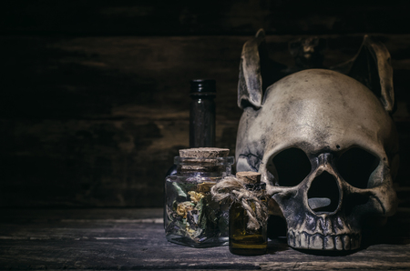 Magic potion and human skull on magic table background. Witchcraft concept. Фото со стока