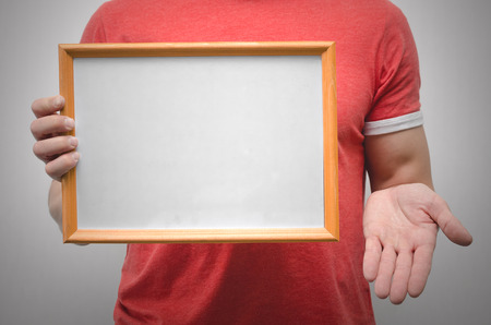 Man is holding a blank diploma or certificate frame border with copy space isolated on gray background.