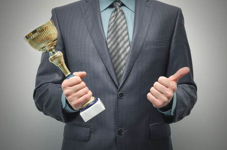 Businessman is holding a golden award trophy in the hands and is showing a thumbs up isolated on gray background.