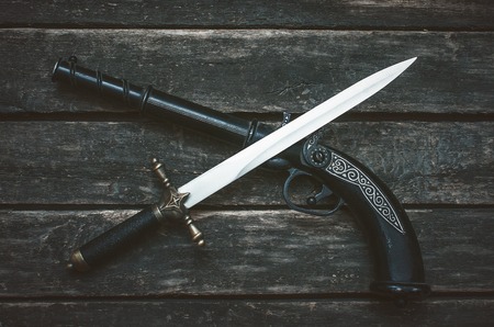 Musket gun and dagger knife on wooden table background.