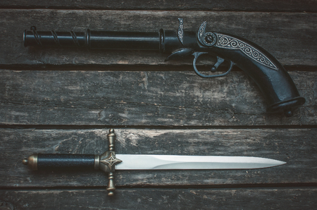 Musket gun and dagger knife on wooden table background with copy space. Фото со стока