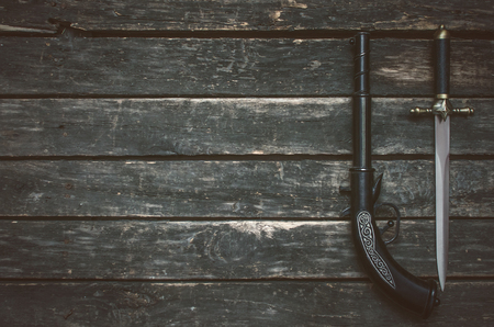 Musket gun and dagger knife on wooden table background with copy space. Stock Photo