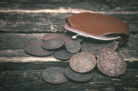 Wallet and old money coins of Russian empire on wooden table background.