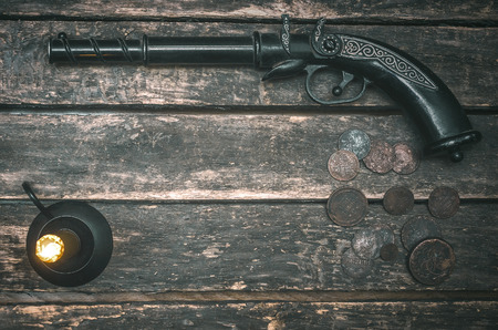 Musket gun, money and burning candle on wooden table background. Duel.