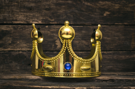 Golden royal crown on the wooden throne background. Authority concept background. Stockfoto