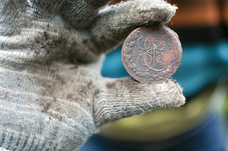Aged 5 kopeks coin of Russian empire in the hand of coin finder. Treasure hunting concept. In search of a lost treasure.