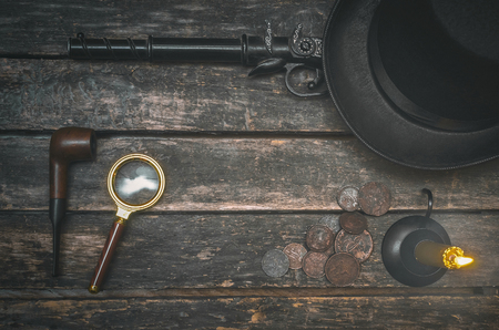 Musket gun, smoking pipe, magnifying glass, money, bowler hat and burning candle on wooden table background. Detective agent table.
