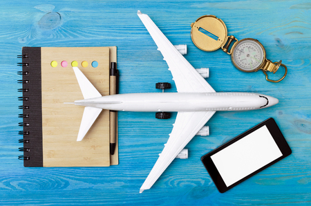 Toy airplane, blank page notepad, navigation compass and blank screen mobile phone on blue table background. Reklamní fotografie