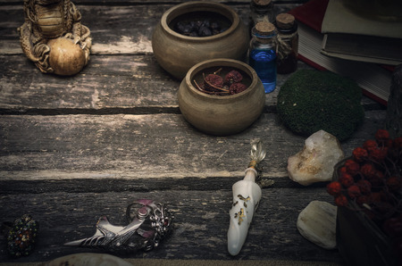 Magic potion preparation on the table of magician. Witchcraft or druidism concept background.