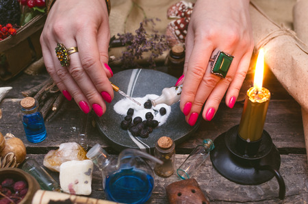 Witch woman is preparing a magic potion on paranormal table background. Witchcraft concept.