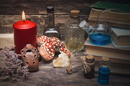 Magic potion in the vial on the wizard table. Witchcraft concept. Essential oil bottles and old books. Herbal medicine.